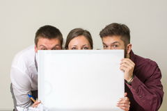 Team hiding behind white board Royalty Free Stock Images