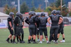 High School Football Team Huddle. A team of high school football players huddle together as they discuss their strategies royalty free stock images