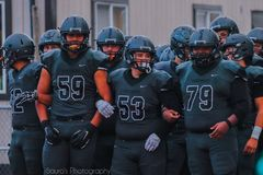 High School Football Team. A team of high school football players huddled together royalty free stock image