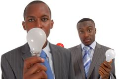 Team of Ideas. This is an image of two businessmen offering up some ideas, represented by the light bulbs. (Light bulb colors are white and red Stock Images