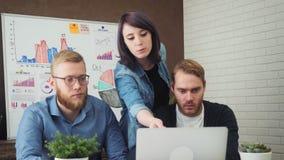 Team il lavoro con il computer portatile mentre si siedono allo scrittorio in ufficio creativo video d archivio