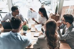 Team of innovators. Top view of young modern people in smart casual wear discussing business while working in the creative office stock image