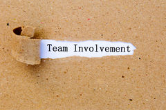 Team Involvement - printed text underneath torn brown paper Stock Photos