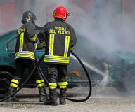 Team of Italian fire brigade extinguished the car fire. After the car accident with the words in the jacket that means FIREMEN in Italian language royalty free stock images