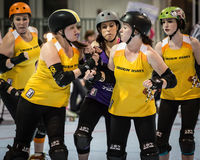 Team Jamming. Redding, California-February 21, 2015: Lava City skaters (yellow) set up a jam during a flat track bout with the Shasta  Roller Derby Girls in Royalty Free Stock Photography