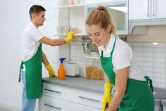 Team of janitors cleaning kitchen. In house royalty free stock image