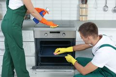 Team of janitors cleaning kitchen oven royalty free stock image