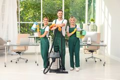 Team of janitors with cleaning supplies stock photo