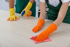 Team of janitors cleaning table in kitchen. Closeup royalty free stock photo
