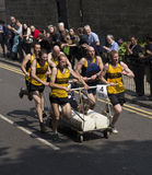 Bed Race. Photograph of a bed race taking place in Knaresborough uk.  Showing a team of 6 men pushing a bed along the streets in this annual competition Royalty Free Stock Images