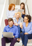 Team with laptop and tablet pc on staircase Stock Images