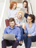 Team with laptop and tablet pc on staircase Stock Photos