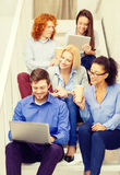 Team with laptop and tablet pc on staircase Stock Photography