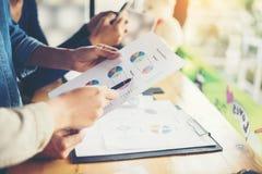 team le mani della donna di affari che funzionano e che tengono il grafico commerciale inf Immagine Stock