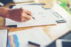 team le mani della donna di affari che funzionano e che tengono il grafico commerciale inf Fotografie Stock