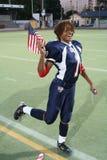 Team le pose del giocatore di football americano degli S.U.A. con la bandiera americana Fotografia Stock