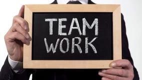 Team le travail écrit sur le tableau noir dans des mains d'homme d'affaires, coopération réussie photos stock