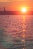 Team le travail des jeunes hommes dans un bateau de rangée silhouetté au coucher du soleil Belles grandes fusées de lumière du so Image stock