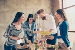 Team le travail Les amis nettoient une table avec des plats et des verres Image libre de droits