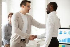 Team leader or boss promoting successful manager handshaking exp. Caucasian team leader or company boss promoting successful african manager handshaking royalty free stock photography