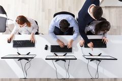 Team Leader Giving Training To His Call Center Operator. Elevated View Of Team Leader Giving Training To His Call Center Operator In Office stock image