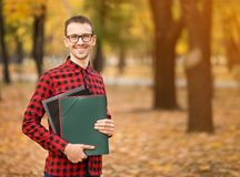 Team leader in glasses with folders go by autumn park. To office stock image