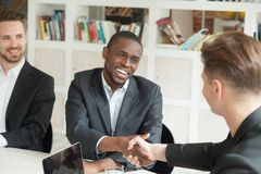 Team leader greeting black colleague with promotion. Caucasian businessman welcoming african american colleague by handshaking at meeting. Team leader greeting Royalty Free Stock Images