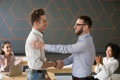 Team leader handshaking employee congratulating with professiona. L achievement or career promotion, thanking for good project result while team supporting stock image