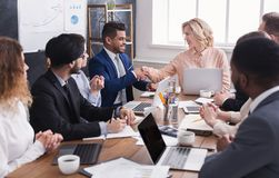Team leader handshaking employee congratulating with professional achievement. At meeting stock photo