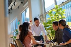 Team leader meeting with young asian employees in smart casual wear.  stock images