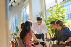 Team leader meeting with young asian employees in smart casual wear.  royalty free stock photos