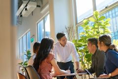 Team leader meeting with young asian employees in smart casual wear.  stock photo