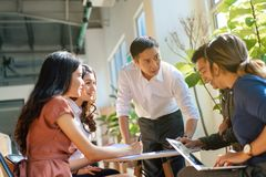 Team leader meeting with young asian employees in smart casual wear.  stock photography