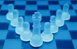 Team leader teamwork. King as team leader in this teamwork business concept using blue crystal chess pieces Royalty Free Stock Image