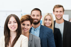Team leadership. Conceptual image of team leadership with a group of professional successful young business men and women standing in a line headed by two Stock Photos