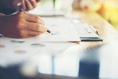 team les mains de femme d'affaires fonctionnant et tenant le graphique de gestion FNI Photographie stock