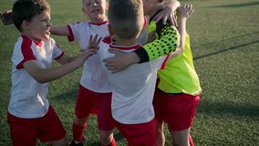 Team of little boys soccer players are embracing. On field of stadium stock video footage