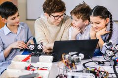 Happy children learn programming using laptops on extracurricular classes royalty free stock images