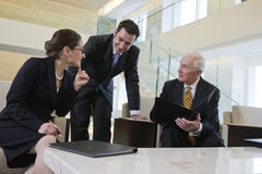 Team in lobby meeting to review paperwork. Royalty Free Stock Photography