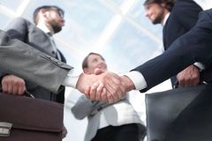 Team looking at a business handshake partner. royalty free stock image