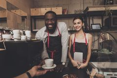 Smiling black guy in apron gives cup of cooked coffee to visitor in cafe. Confectionery. Barista. stock photos