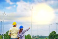 A team of male and female engineers together develop wind power generate electricity. A team of male and female engineers together develop wind power to generate stock image