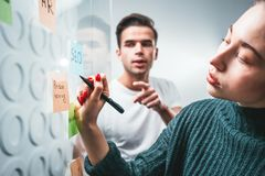 Team of male and female project managers discussing ideas while collaborating on project sharing creative solution standing behind. Glass wall with sticky notes stock photo