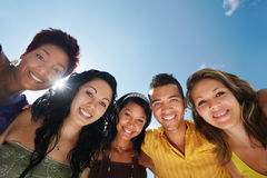 Team of man and women embracing, smiling at camera stock photo
