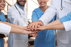 Team of medical doctors putting hands together indoors. Unity concept royalty free stock images