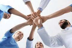 Team of medical doctors putting hands together. Unity concept stock image
