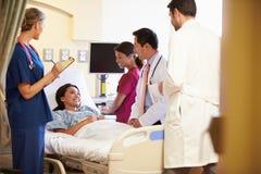Team Meeting Around Female Patient médical dans la chambre d'hôpital photographie stock