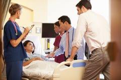 Team Meeting Around Female Patient médico na sala de hospital imagens de stock royalty free