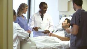 Team Meeting Around Male Patient medico nella stanza di ospedale video d archivio