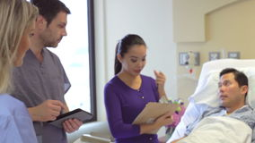 Team Meeting Around Male Patient medico nella stanza di ospedale archivi video